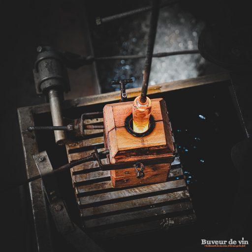 Introduction du verre en fusion dans le moule en bois